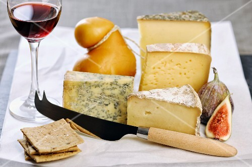 Assorted types of cheese with figs, crackers and a glass of port