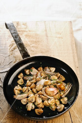 Fried mushrooms with herbs in a frying pan
