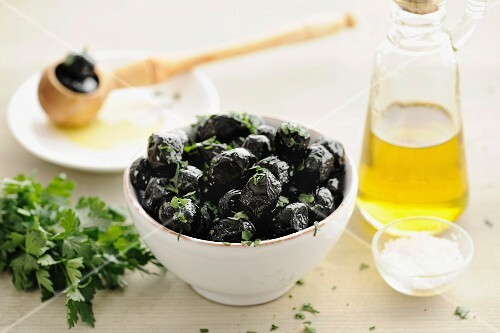 Black olives in a bowl with parsley and olive oil