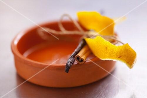 Lemon peel, a cinnamon stick and a vanilla pod on a ramekin