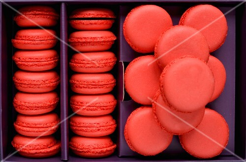 Freshly baked red macaroons in a purple box