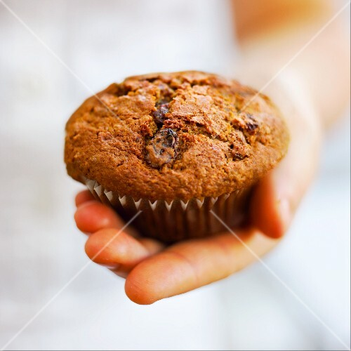 Hand holding a raisin muffin