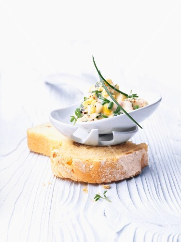 Egg mayonnaise in a dish on a slice of white bread