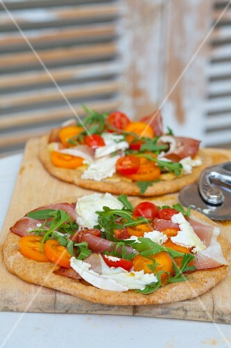 Pizzas topped with rocket, prosciutto, goat's cheese and tomatoes