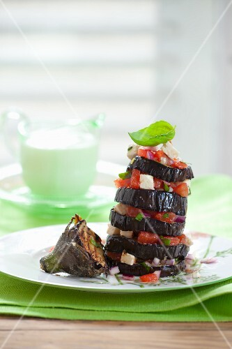 A tower of grilled aubergine slices with tomatoes and feta