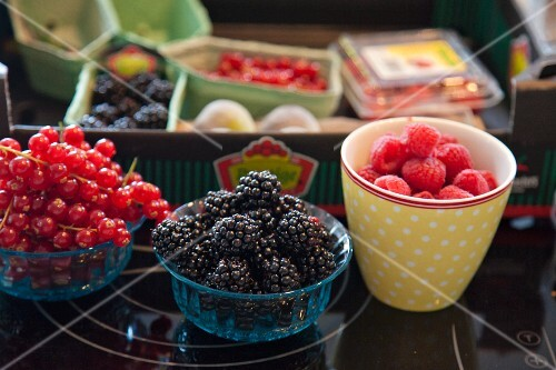 Assorted berries in bowls and packaged in a crate