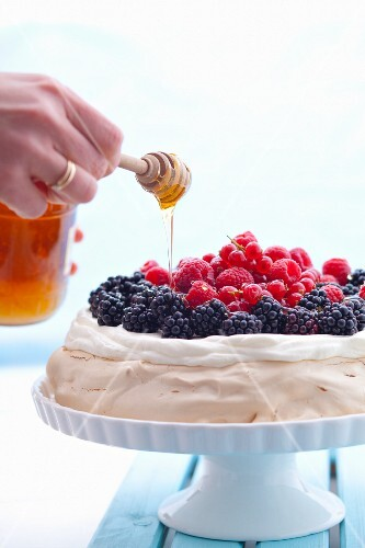Honey being drizzled over a berry pavlova