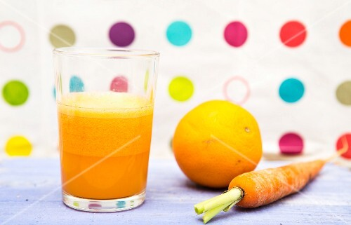 A glass of carrot and orange juice next to a fresh orange and a fresh carrot