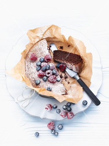 Chocolate and nut cake with berries and icing sugar