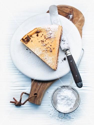 A slice of ricotta & espresso layer cake with icing sugar