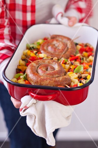 Woman holding baking dish with spiral pork sausages on baked vegetables