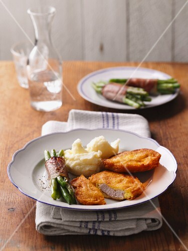 Breaded pork schnitzel with mashed potatoes and green beans wrapped with bacon