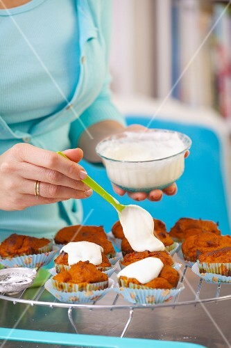 A woman spreading glacé icing on carrot muffins
