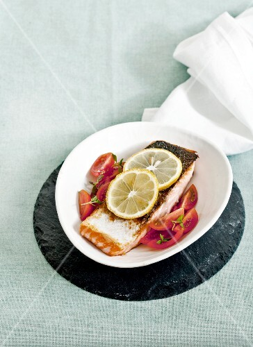 Salmon fillet with tomato salad and lemons