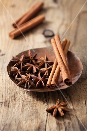 Star anise and cinnamon sticks in a dish on a wooden surface