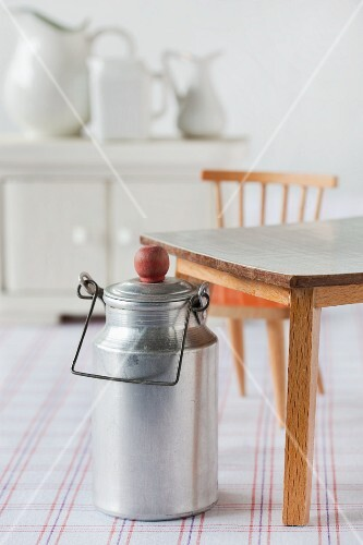 Still-life of dolls' house furniture: milk can, table, chair, sideboard and jugs on checked cloth