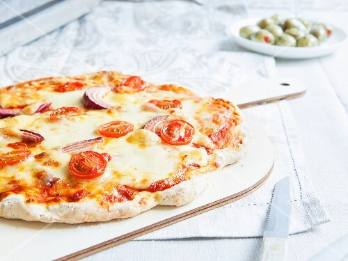 Vegetarian stone-baked pizza topped with tomatoes and red onions