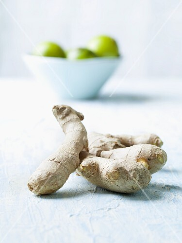 Fresh root ginger; in the background a bowl of limes