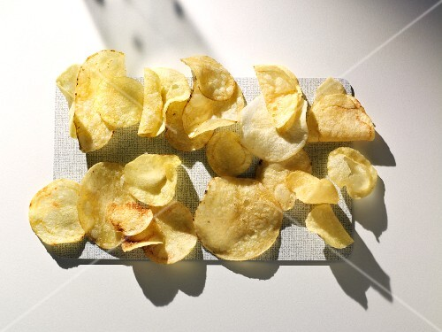 Potato crisps on a cutting board (view from above)