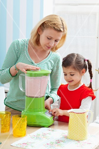 A mother and daughter preparing a strawberry milkshake