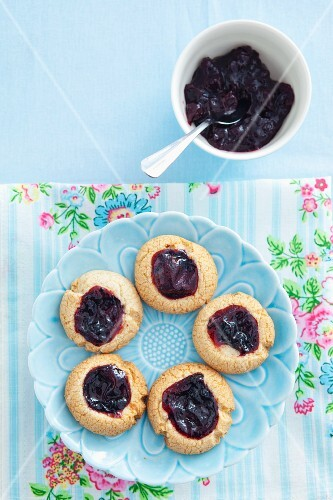 Biscuits filled with blackcurrant jam on a blue plate
