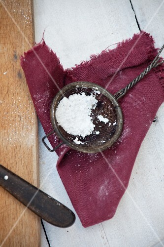 Icing sugar in an old sieve on a cloth