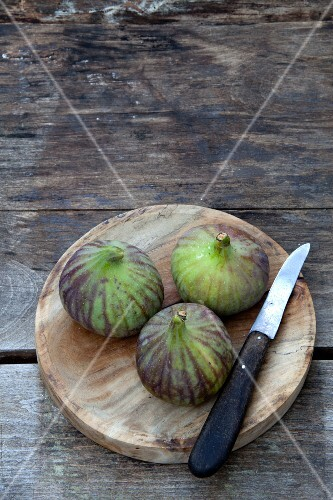 Three fresh figs on a round wooden board with a knife