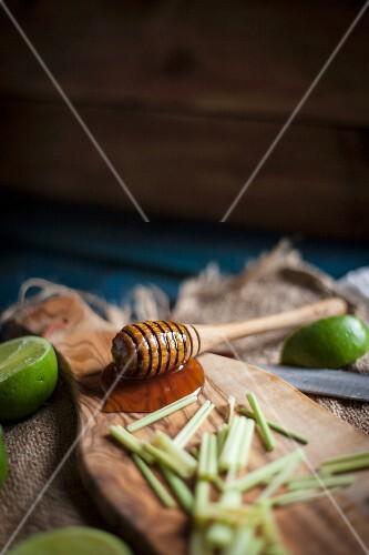 Honiglöffel mit Honig, Zitronengras und Limetten