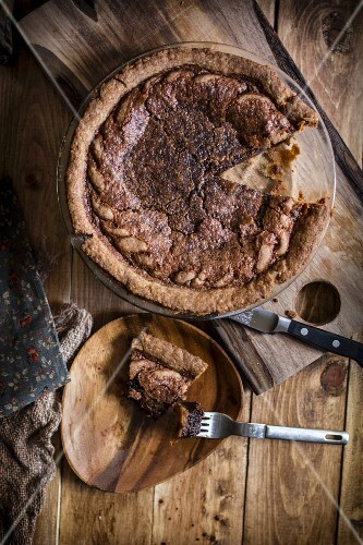 Chocolate Chess Pie with a Slice Removed; Piece of a Wooden Dish with Bite Taken Out