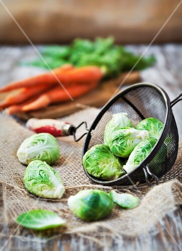 Organic Raw Brussels Sprouts in a Strainer; Carrots