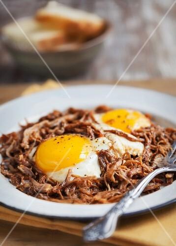 Ein Teller mit gebratenen Eier auf Pulled Pork