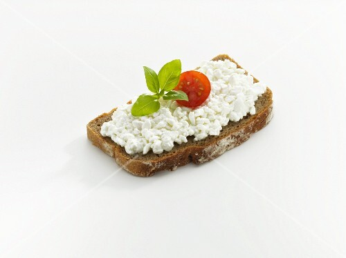 Bread topped with cottage cheese, tomato and basil