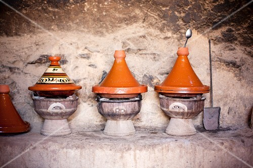 Several tagine pots on small barbecue ovens