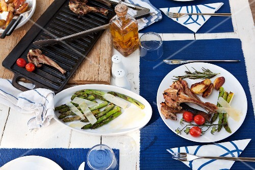 Grilled lamb chops with green asparagus, cherry tomatoes and roast potatoes on a table outdoors
