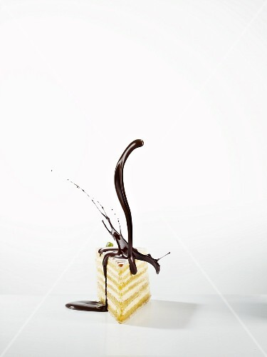 A slice of cake with a splash of chocolate sauce