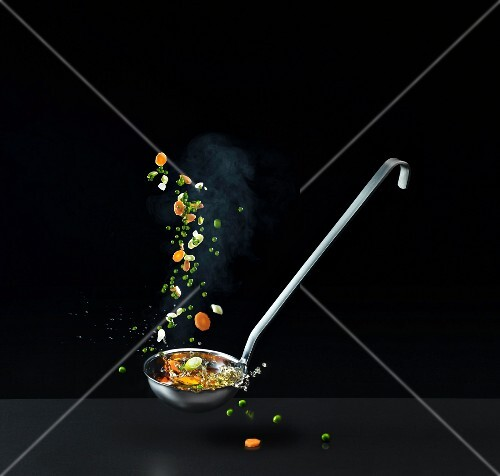 Mixed vegetables falling into a ladle of vegetable soup