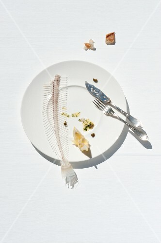 Fish bones from a sole and a lemon wedge on a plate with fish knife and fork