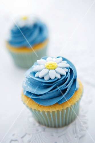 Cupcakes with blue buttercream icing and a sugar flower
