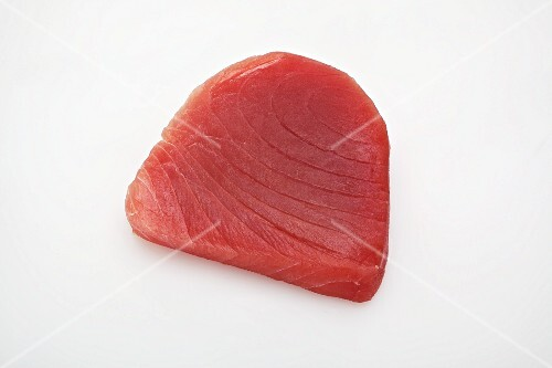 Raw tuna steak on a white surface