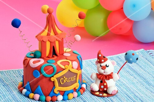 A party cake designed as a circus tent and a fondant bear with a cake pop