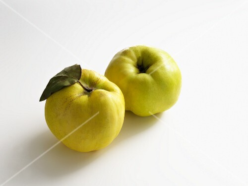 Two quinces on a white surface