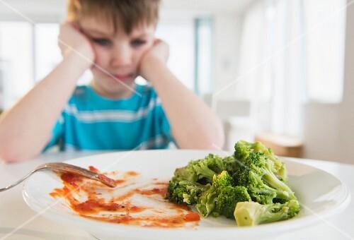 Junge sitzt grimmig vor Teller mit Gemüseresten