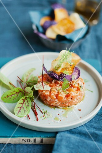 Salmon tartar with fresh herbs and colourful potato chips