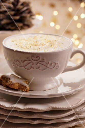 Cappuccino with gold sprinkles and a star-shaped cinnamon biscuit