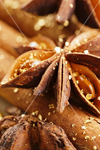Star anise and cinnamon sticks with gold dust (close-up)