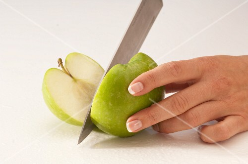 A woman cutting a green apple in half with a knife