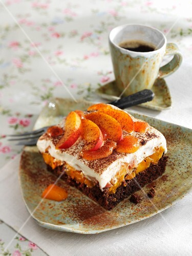A square of chocolate cake topped with apricots and thickened cream