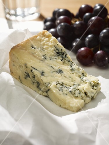 Blue Stilton on white baking parchment, with red grapes