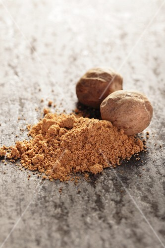 Nutmegs and ground nutmeg on a grey surface