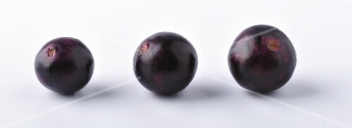Three acai berries against a white background